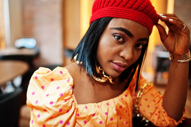 赤いフレンチベレー帽、大きなゴールドのネックチェーン水玉ブラウスのエレガントなアフロアメリカン女性が屋内でポーズします。