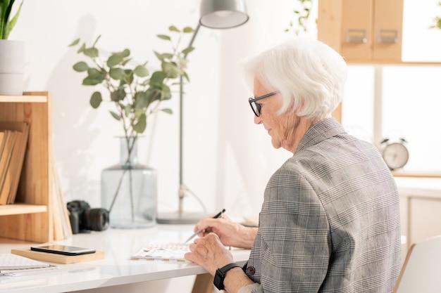 Элегантная женщина-офисный работник в возрасте, склонившись над открытым блокнотом на столе, читая пункты рабочего плана или повестки дня