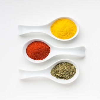Elegant aligned spoons with spices powder