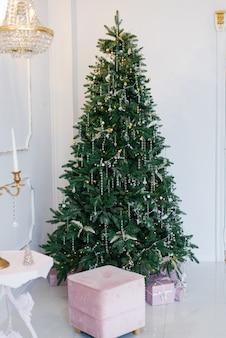 밝은 거실 내부의 우아하고 아름다운 크리스마스 트리.