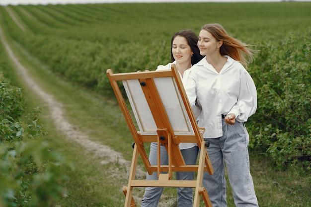 Элегантные и красивые девушки рисуют в поле