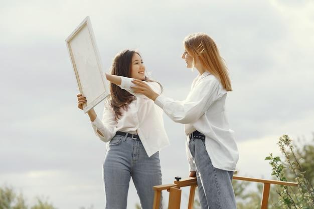 フィールドで絵画するエレガントで美しい女の子
