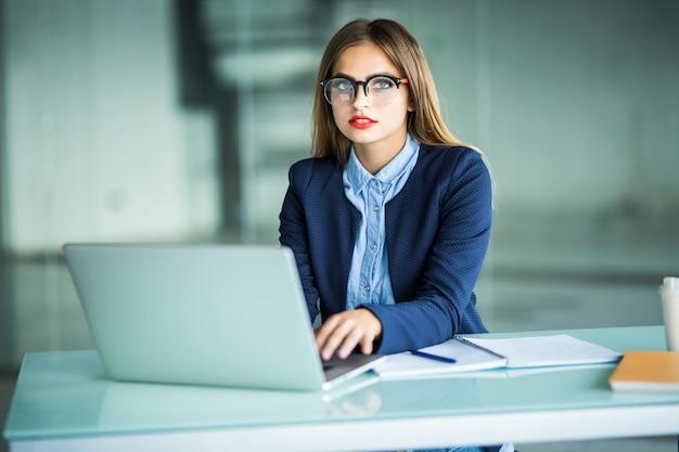 Элегантная и жизнерадостная бизнес-леди. веселая молодая красивая женщина в очках смотрит с улыбкой, сидя на своем рабочем месте