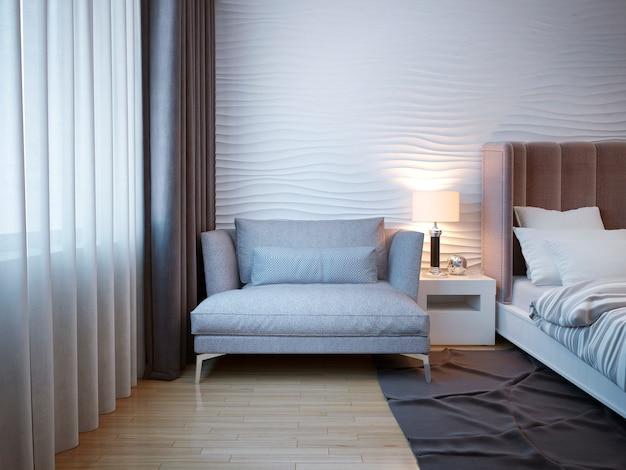 金属製の脚を備え、モダンなベッドルームのベッドサイドテーブルの近くに立っているバッドルームインテリアのエレガントで快適なソファ。