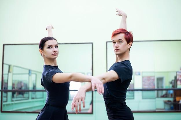 ライトホールで踊りを練習するエレガントで優雅なバレエダンサー