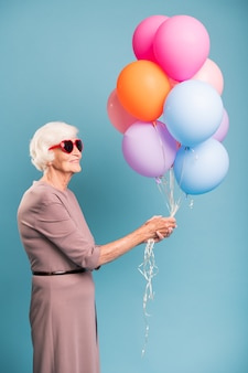 カラフルな風船の束を保持しているエレガントで優雅なシニア女性