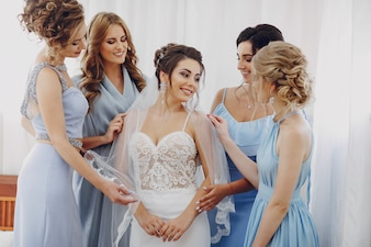 Elegant and stylish bride along with her four friends in blue dresses standing in a room