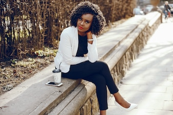 Elegant and stylish dark-skinned girl with curly hair and in a white jacket sitting