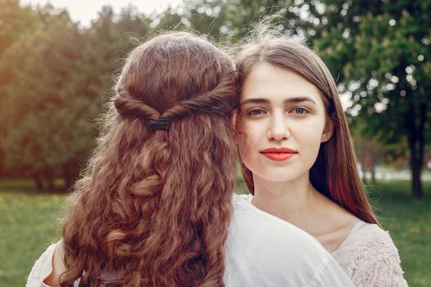 Элегантные и стильные сестры в весеннем парке