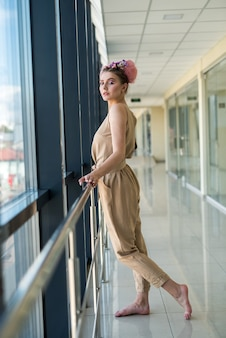 長い廊下の中でポーズをとってピンクのドレスを着たエレガントで若い女性