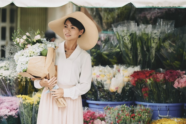 Elegant asian lady with large bouquet waiting in street in front of flower shop