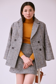 Elegant asian woman in fashionable woolen coat and classic skirt