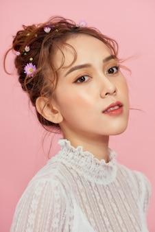 メイクや髪型のエレガントなアジアの女性の女性。ピンクの上のファッションの女の子モデル