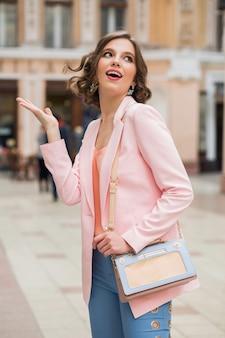 Элегантная привлекательная эмоциональная женщина с вьющейся прической гуляет по городу со стильной сумочкой