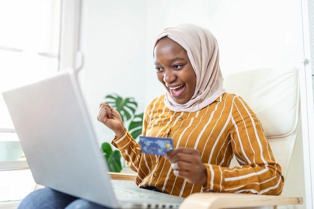 自宅のリビングルームでオンラインショッピング情報を検索するモバイルラップトップを使用してエレガントな魅力的なイスラム教徒の女性。オンラインショッピングで商品を購入する幸せな女性の肖像画。クレジットカードで支払う