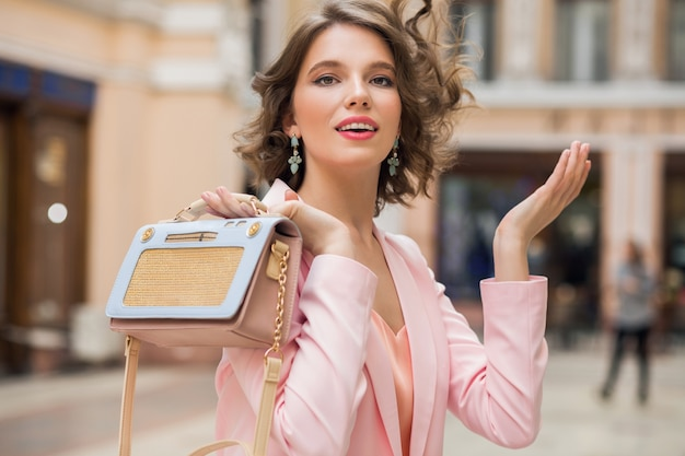 Elegant attractive smiling woman with curly hairstyle walking in city with stylish handbag in pink