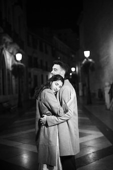 Elegant attractive woman hugging with young man on street at night