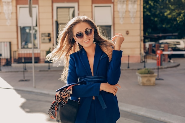 青いスタイリッシュなスーツとサングラスを身に着けているエレガントな魅力的な女性がハンドバッグを持って通りを歩く