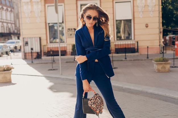 Elegant attractive woman wearing blue stylish suit and sunglasses walking in street holding handbag