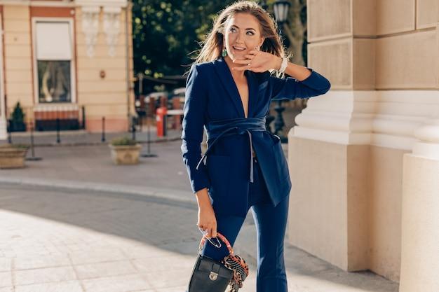 Elegant attractive woman wearing blue stylish suit walking in street holding handbag