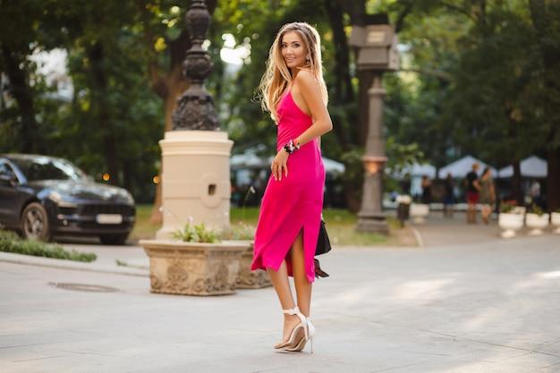 Элегантная привлекательная женщина в розовом сексуальном летнем платье гуляет по улице с сумочкой