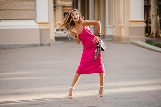 Elegante donna attraente che indossa un abito estivo sexy rosa che cammina nella borsa della holding della strada