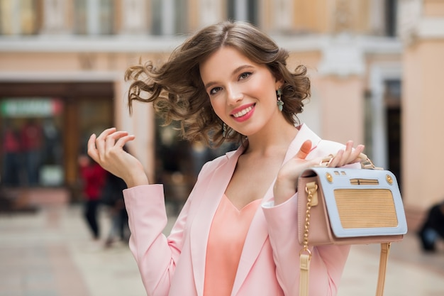 スタイリッシュなハンドバッグで街を歩いてカメラを見て巻き毛のエレガントな魅力的な女性