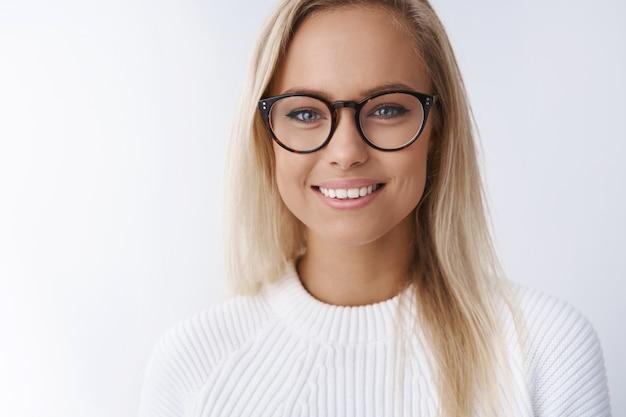 Elegante e attraente giovane donna d'affari con gli occhiali sorridente felice, soddisfatta della nuova montatura di occhiali che guarda amichevole felicemente alla macchina fotografica raggiungendo il successo pronto a condividere suggerimenti sul muro bianco.