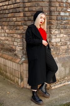 革のブーツの赤いシャツの黒いベレー帽のスタイリッシュなロングコートでエレガントな魅力的な若い女性のブロンドは、街のヴィンテージのレンガの壁の近くに立っています