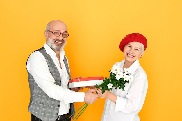 Elegant bald unshaven man pensioner in spectacles giving birthday gift to his adorable middle aged wife