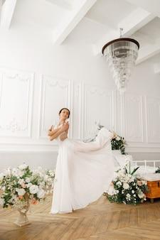 침대 근처의 밝은 클래식 홀에서 우아한 발레리나 춤