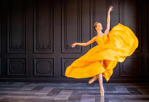 포인트 슈즈의 우아한 발레리나가 긴 노란색 치마를 입고 춤을 춥니 다.