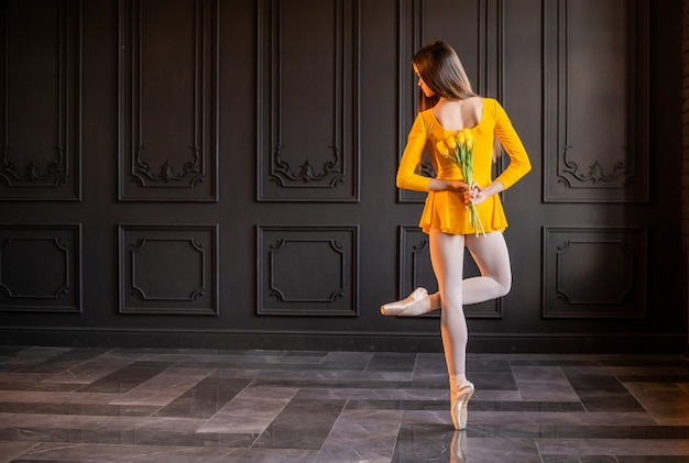 포인트 슈즈의 우아한 발레리나가 어두운 회색 배경에 튤립 꽃다발과 함께 춤을 춥니 다.