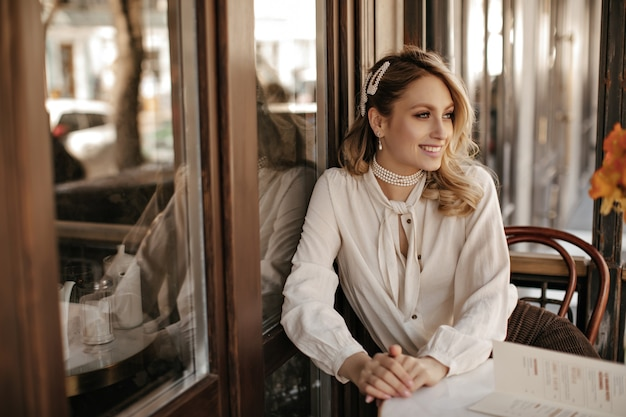Elegant beautiful blonde woman in white stylish blouse, pearl jewelry smiles widely, looks away and sits by little table in street cafe