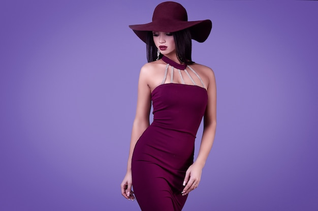 Elegant beautiful brunette woman in a violet dress and wide hat