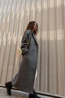 긴 유행 코트에 곱슬머리를 한 우아한 아름다운 소녀가 핸드백을 들고 금속 벽 근처 거리를 걷습니다.