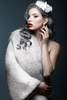 실버 곱슬 머리와 베일 우아한 아름다운 소녀. 겨울 이미지. 아름다움 얼굴. 회색 배경에 스튜디오에서 찍은 사진.