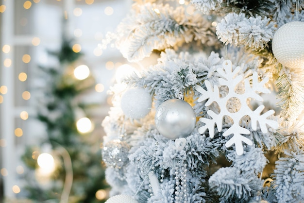 Elegant beautiful silver christmas tree with white and gold balloons close up