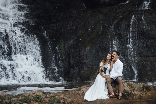 Elegant beautiful wedding couple posing near beautiful grand waterfall in mountain.
