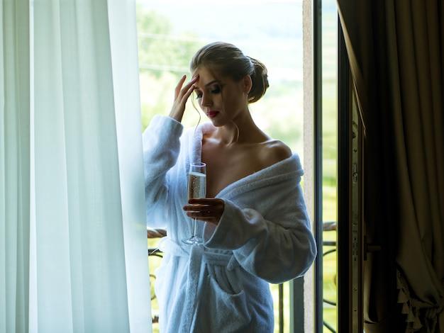우아한 아름다운 여자. 여성 슬림 모델. 패션 사진. 샴페인 목욕 가운 여자