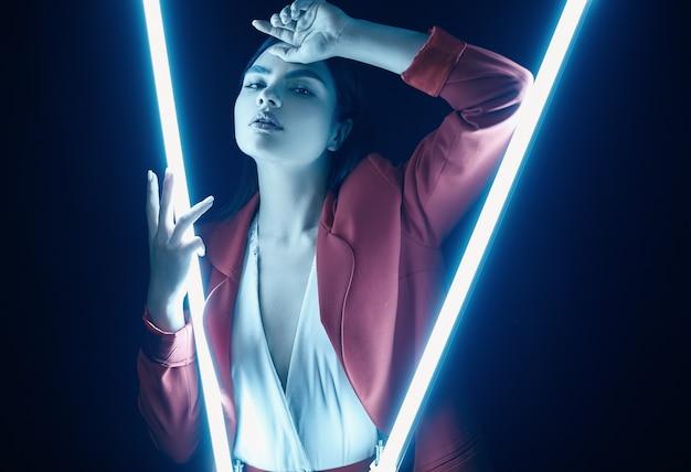 ネオンでポーズをとって赤いファッショナブルなスーツでエレガントな美しい女性