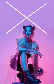 Elegant beautiful woman in a raincoat around colorful bright neon