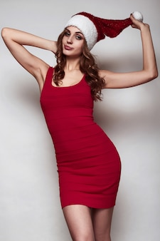 Elegant beautiful woman in a red dress and christmas hat