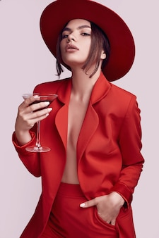 Elegant beautiful woman in a red fashionable suit and hat with cocktail
