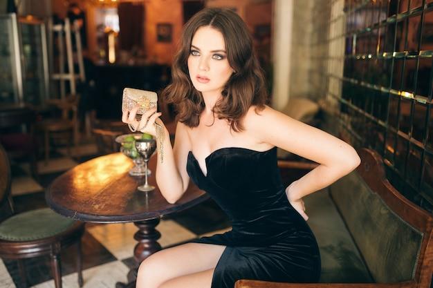 검은 벨벳 드레스, 이브닝 가운, 풍부한 세련된 아가씨, 우아한 패션 트렌드, 섹시한 자신감, 황금 지갑을 들고 빈티지 카페에 앉아 우아한 아름다운 여인