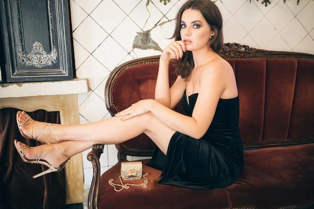 검은 벨벳 드레스, 이브닝 가운, 풍부한 세련된 아가씨, 우아한 패션 트렌드, 섹시한 매혹적인 외모, 매력적인 스키니 인물, 굽 신발을 신고 빈티지 카페에 앉아 우아한 아름다운 여인