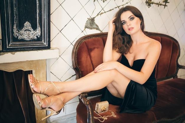 黒のベルベットのドレス、イブニングドレス、リッチでスタイリッシュな女性、エレガントなファッショントレンド、セクシーな魅惑的な外観、魅力的なスキニーフィギュア、ヒールの靴を履いてヴィンテージカフェに座っているエレガントな美しい女性
