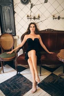 Элегантная красивая женщина сидит в винтажном кафе в черном бархатном платье, вечернем платье, богатая стильная дама, элегантный модный тренд, соблазнительный сексуальный вид, привлекательная худощавая фигура