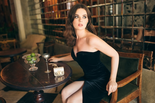 검은 벨벳 드레스, 이브닝 가운, 풍부한 세련된 아가씨, 우아한 패션 트렌드, 데이트에 그녀의 남자 친구를 기다리는 빈티지 카페에 앉아 우아한 아름다운 여인, 관능적 인 모습