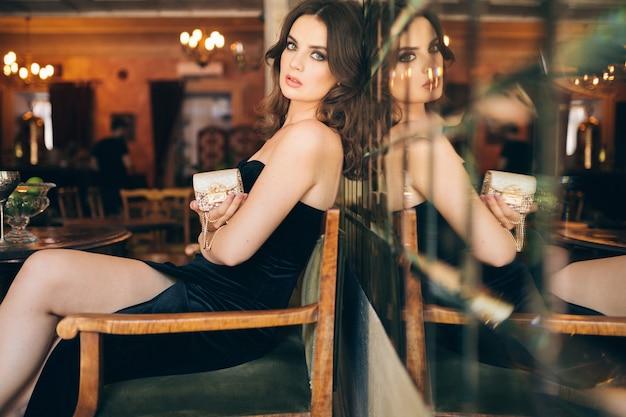 검은 벨벳 드레스, 이브닝 가운, 풍부한 세련된 아가씨, 우아한 패션 트렌드, 날짜를 기다리고, 작은 황금 핸드백을 손에 들고 빈티지 카페에 앉아 우아한 아름다운 여인